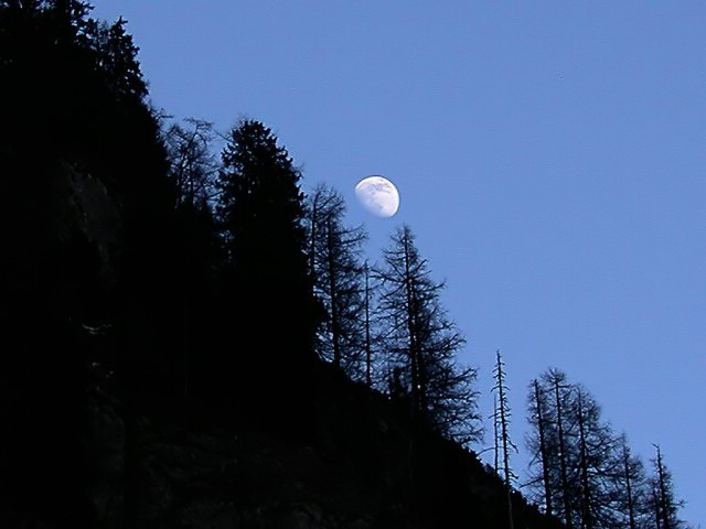 Moon rising over italian Dolomites mountains